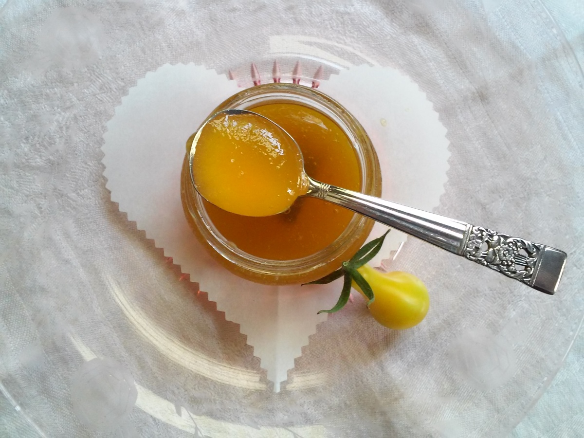 Yellow Tomato Jam in jar on spoon